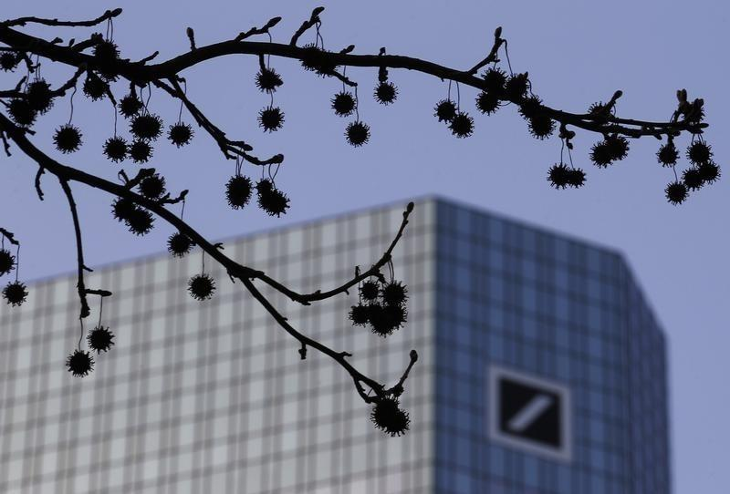 The logo of Germany's largest business bank, Deutsche Bank, is seen at the bank's headquarters behind twigs in Frankfurt