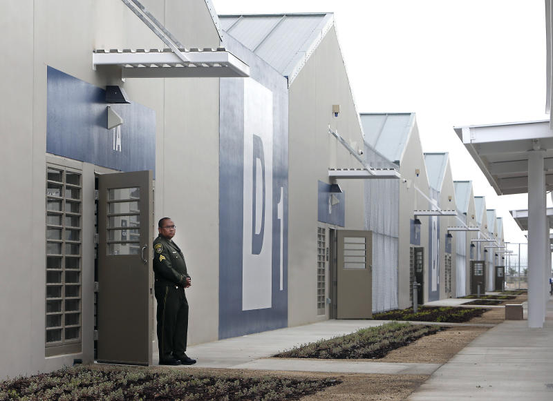 FILE - In this June 25, 2013 file photo, a correctional officer stands outside of one of the secure housing units at the new California Correctional Health Care Facility in Stockton, Calif., during dedication day festivities. Legionnaires' disease bacteria that killed one inmate and sickened another is more widespread than expected in a California state prison, officials said Wednesday, April 17, 2019, citing new test results. Preliminary results found the bacteria in the water supply at a prison medical facility in Stockton and at two neighboring youth correctional facilities, said Corrections Department spokeswoman Vicky Waters. (AP Photo/Rich Pedroncelli, File)
