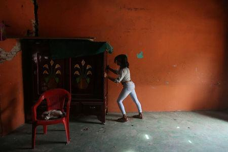 Natashia, 19, an indigenous Zapotec transgender woman also know as Muxe, moves a furniture inside her house destroyed after an earthquake that struck on the southern coast of Mexico late on Thursday, in Juchitan, Mexico, September 10, 2017. REUTERS/Edgard Garrido