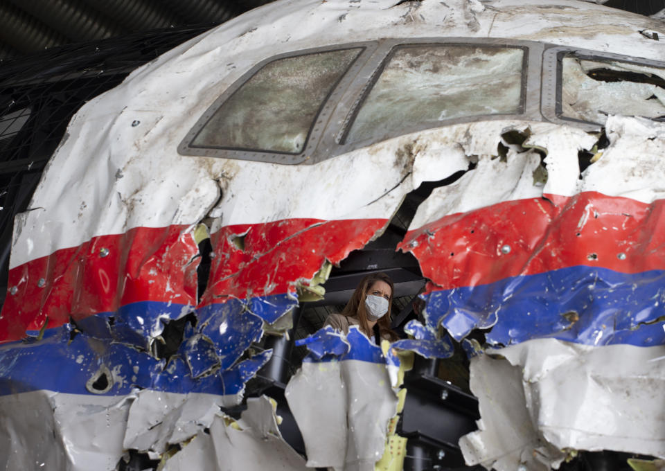 FILE- In this Wednesday, May 26, 2021, file photo trial judges and lawyers view the reconstructed wreckage of Malaysia Airlines Flight MH17, at the Gilze-Rijen military airbase, southern Netherlands. The international team investigating the downing seven years ago of Malaysia Airlines flight MH17 over eastern Ukraine appealed Thursday for Russians in the city of Kursk to come forward with information about the deployment of the missile that the investigators say downed the plane, killing all 298 people on board. (AP Photo/Peter Dejong, File)