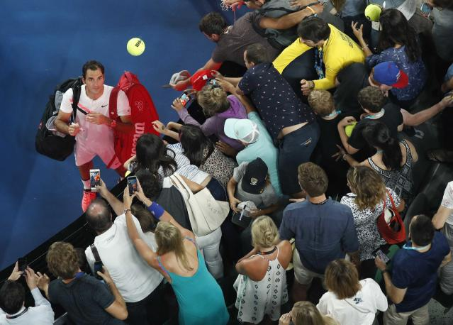 Tennis - Australian Open - Rod Laver Arena, Melbourne, Australia, January 20, 2018. Roger Federer of Switzerland throws a ball into the crowd as he signs autographs after winning against Richard Gasquet of France. REUTERS/Edgar Su TPX IMAGES OF THE DAY