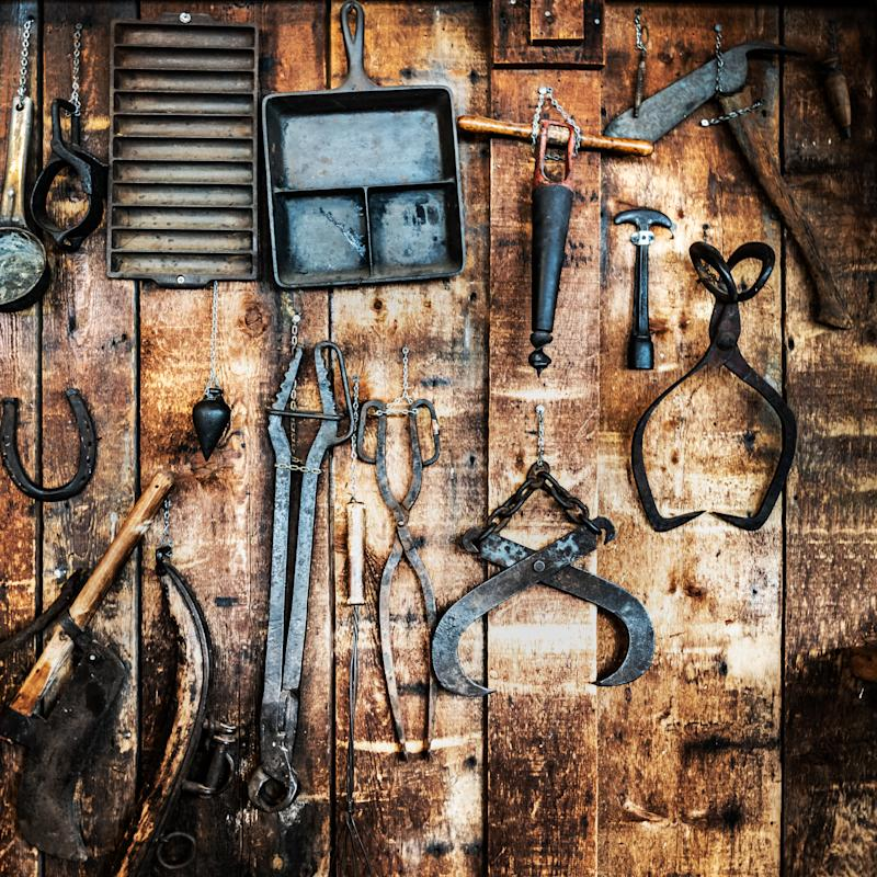 Collection of antique metal tools displayed on a wooden wall