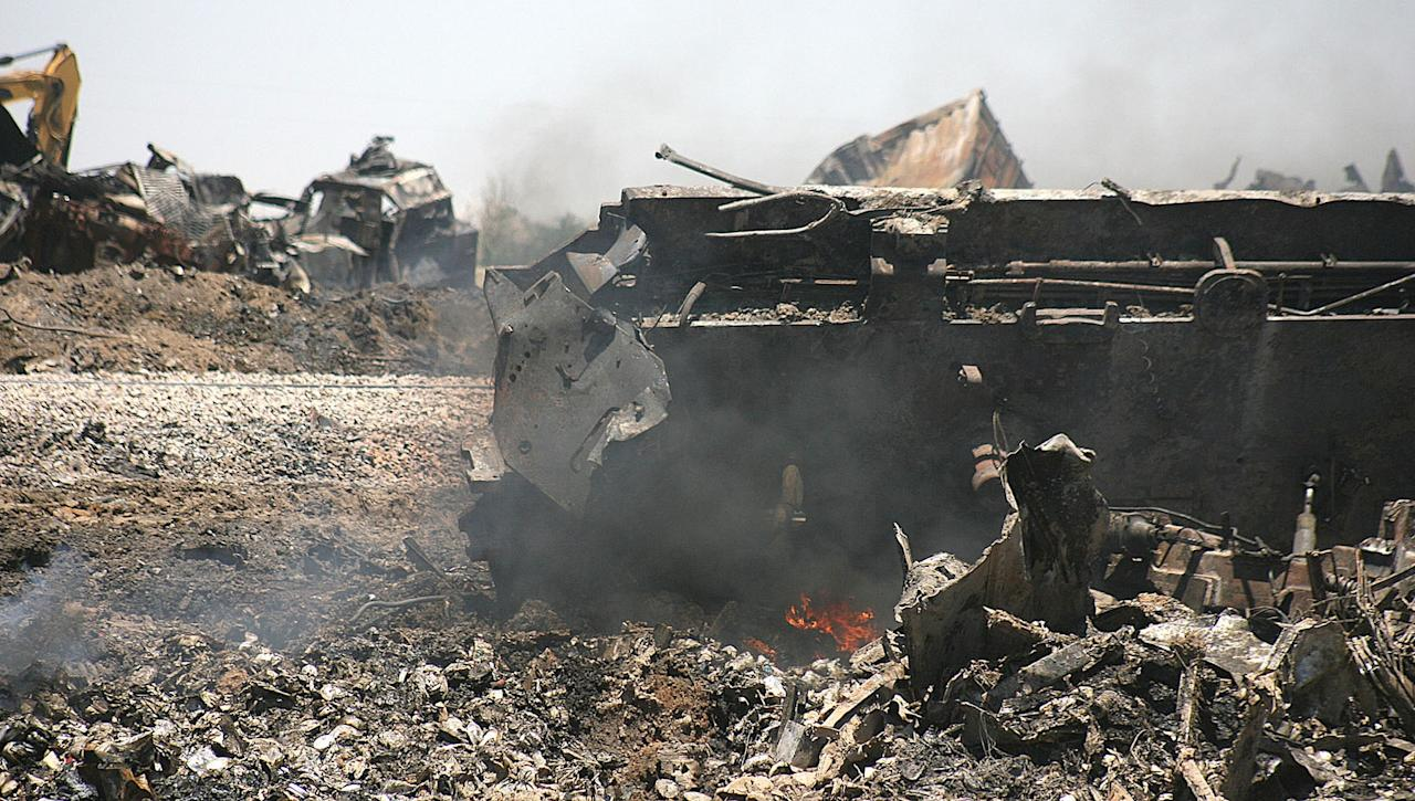 Train wreckage still smolders on Monday, June 25, 2012, near Goodwell, Okla. Two Union Pacific trains collided on Sunday, June 24, 2012, killing two crew members and a conductor. (AP Photo/The Guymon Daily Herald, Shawn Yorks)