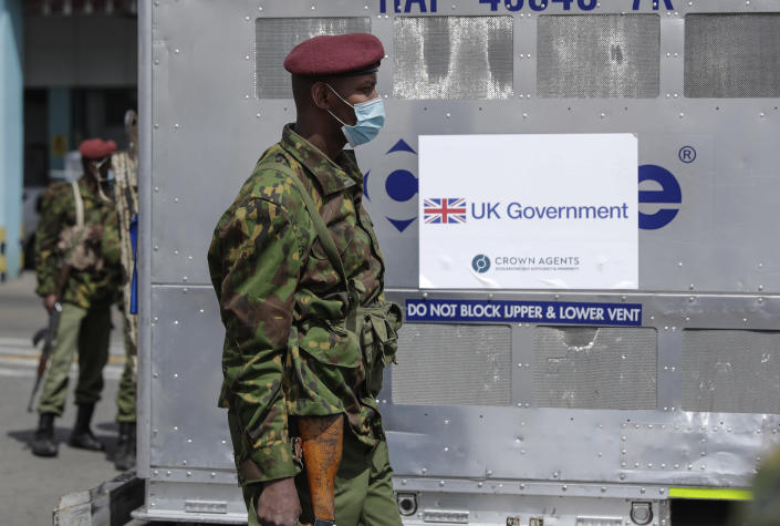 FILE - In this July 31, 2021, file photo, Kenyan soldiers guard the 410,000 doses of COVID-19 vaccines donated by the United Kingdom Government at the Jomo Kenyatta International Airport, Nairobi, Kenya. Authorities in India and some African countries are furious over the U.K.'s new COVID-19 travel rules. People vaccinated in many countries, including Kenya, still have to quarantine upon arrival in England. (AP Photo/Brian Inganga, File)