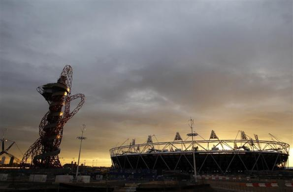 The sun sets behind the Olympic stadium and Anish Kapoor's ArcelorMittal Orbit tower in Stratford, east London, March 5, 2012.