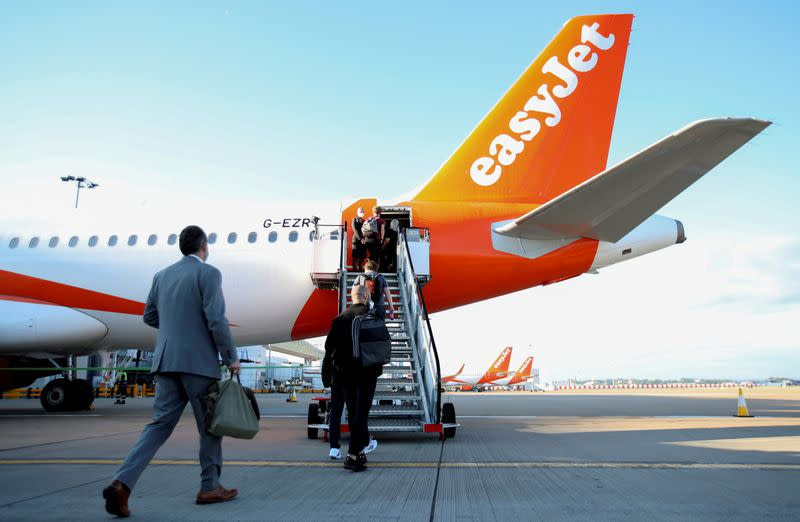 FILE PHOTO: Passengers board a plane as easyJet restarts its operations at Gatwick Airport