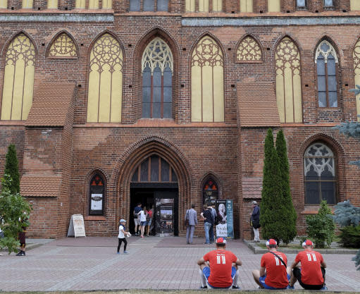 In this photo taken on Thursday, June 21, 2018, Serbia fans sit outside the Kaliningrad Cathedral, which houses a museum dedicated to Immanuel Kant, in Kaliningrad, Russia. In Kaliningrad, a small Russian outpost sandwiched between Poland, Lithuania and the Baltic Sea, philosophy and football are coming together as fans troop through a small museum dedicated to the city and one of its most famous residents - Immanuel Kant. The German philosopher who died in 1804 lived most of his life in Kaliningrad when it was the German city of Koenigsberg - it became part of the Soviet Union after World War II and now serves as an important Russian naval base and is home to a university named for Kant. (AP Photo/Michael Corder)
