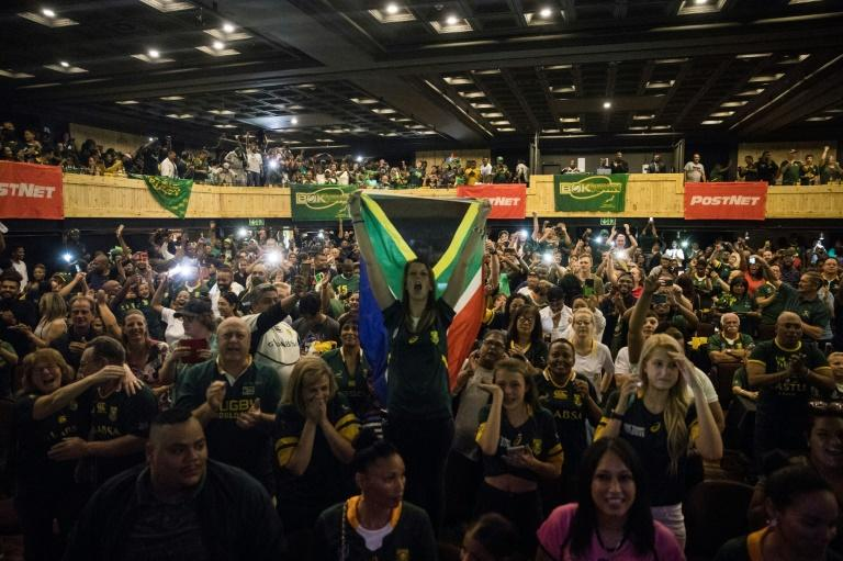 A woman (C) holds a South African flag as a crowd watches the Rugby World Cup final at a Johannesburg theme park last Saturday