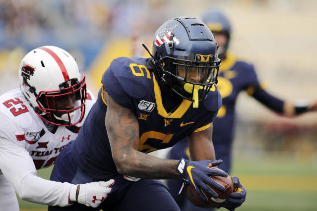 West Virginia's Kennedy McKoy (6) catches the ball in the end zone for a touchdown as Texas Tech's DaMarcus Fields (23) defends during their NCAA college football game in Morgantown, W.Va., Saturday, Nov. 9, 2019. (AP Photo/Chris Jackson)
