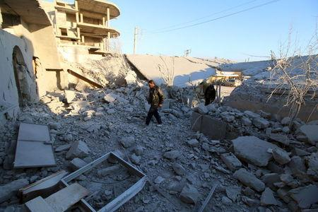 Residents inspect damage after airstrikes by pro-Syrian government forces in Anadan city, about 10 kilometers away from the towns of Nubul and Zahraa, Northern Aleppo countryside, Syria February 3, 2016. REUTERS/Abdalrhman Ismail