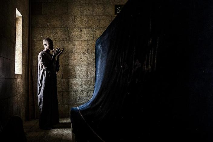 A pilgrim prays before the tomb of Usman Dan Fodio, revered by the Fulani as a holy man (AFP Photo/Luis TATO)
