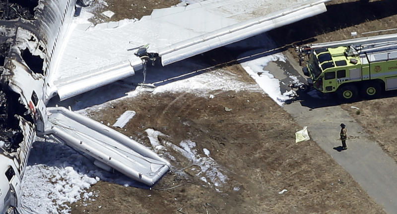 <p> FILE - In this July 6, 2013, aerial file photo, a firefighter stands by a tarpaulin sheet covering a body near the wreckage of the Asiana Flight 214 airplane after it crashed at the San Francisco International Airport in San Francisco, Saturday, July 6, 2013. On Friday, July 19, 2013, the San Mateo County Coroner's Office announced that 16-year-old victim, Ye Meng Yuan, survived the plane crash only to be run over and killed by a firefighters vehicle. (AP Photo/Marcio Jose Sanchez)