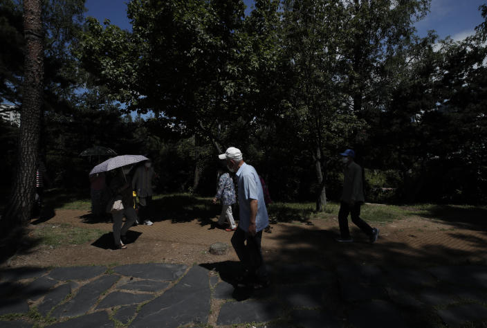 People wearing face masks to help protect against the spread of the new coronavirus walk near a park in Seoul, South Korea, Wednesday, July 15, 2020. (AP Photo/Lee Jin-man)