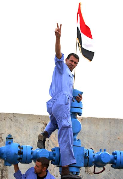 "FILE - In this Dec. 25, 2009 file photo, a worker at the al-Fakkah oil field flashes the ""victory"" sign next to the Iraqi flag in Maysan province, south of Baghdad, Iraq. A senior Iraqi official on Wednesday said his country expects to ramp up oil production to 4.5 million barrels per day by the end of next year from around 3.5 million barrels now, thanks to work by a handful of international oil companies developing the country's prized oil and gas fields. (AP Photo/ Alaa al-Marjani, File)"