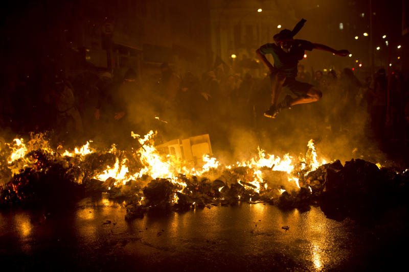 FILE - In this Oct. 7, 2013 file photo, a Black Bloc anarchist jumps over a burning barricade at the Cinelandia square during a march in support of teachers on strike in Rio de Janeiro, Brazil. The Black Bloc, a violent form of protest and vandalism that emerged in the 1980s in West Germany, has become a driving force in Brazil behind protests in recent weeks. The young Brazilians are following the main anti-capitalist tenets of earlier versions, smashing scores of banks and multinational businesses during demonstrations and directly confronting riot police. (AP Photo/Felipe Dana, File)