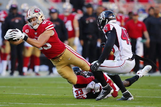 FILE - In this Dec. 15, 2019, file photo, San Francisco 49ers tight end George Kittle, left, runs against Atlanta Falcons defensive back Blidi Wreh-Wilson (33) and linebacker Deion Jones (45) during the first half of an NFL football game in Santa Clara, Calif. Kittle has agreed to a five-year extension with the San Francisco 49ers that reportedly is the richest contract ever at the position. A person familiar with the deal says the sides agreed Thursday, Aug. 13, 2020, on the deal to keep Kittle off the market next offseason. (AP Photo/John Hefti, File)