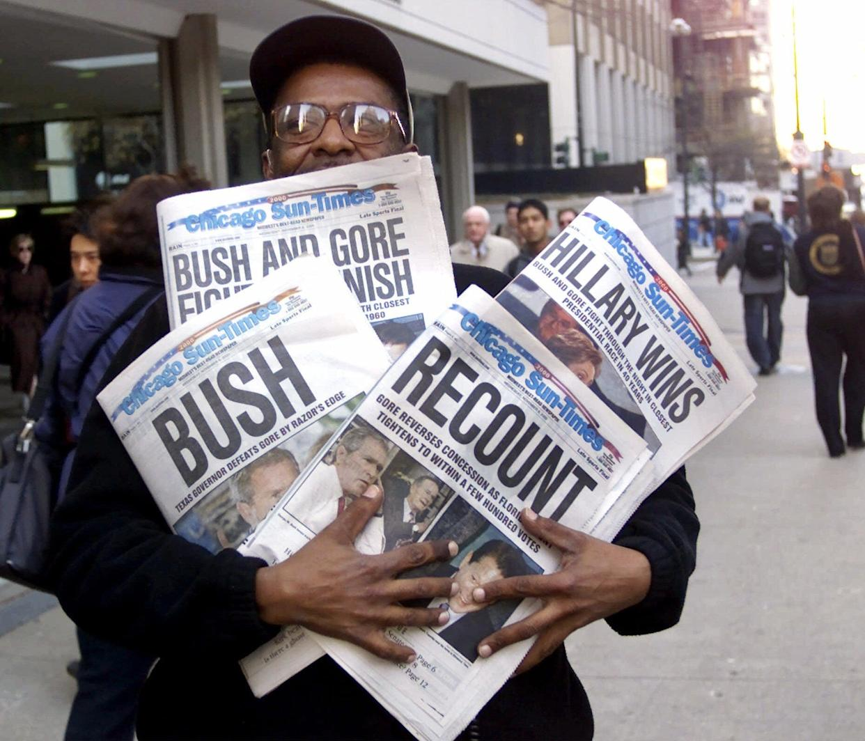 In this Nov. 8, 2000 file photo, Willie Smith holds four copies of the Chicago Sun-Times, each with a different headline, in Chicago, reflecting a night of suspense, drama and changes in following the presidential race between Vice President Al Gore and Texas Gov. George W. Bush.