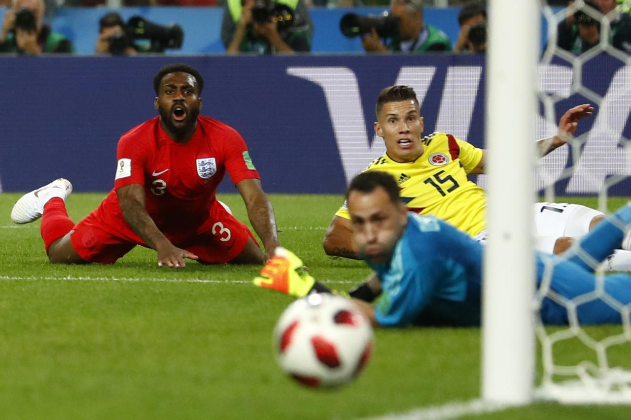 <p>England's Danny Rose, left, reacts as Colombia's Mateus Uribe, right, and goalkeeper David Ospina look the ball passing next to the goalpost during the round of 16 match between Colombia and England at the 2018 soccer World Cup in the Spartak Stadium, in Moscow, Russia, Tuesday, July 3, 2018. (AP Photo/Matthias Schrader) </p>