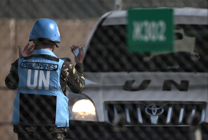 A U.N. peacekeeper from the Philippines UNDOF force works at the Quneitra Crossing between Syria and the Israeli-controlled Golan Heights, Saturday, March, 9, 2013. Syrian rebels freed 21 U.N. peacekeepers on Saturday after holding them hostage for four days, ending a sudden entanglement with the world body that earned fighters trying to oust President Bashar Assad a flood of negative publicity. (AP Photo/Dan Balilty)