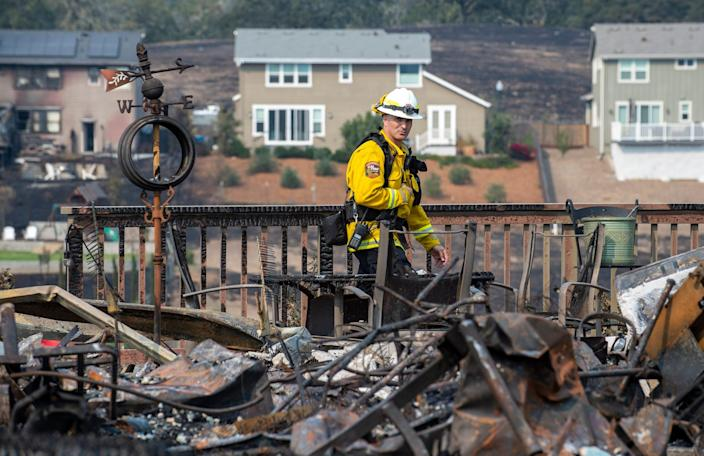 Deputy State Fire Marshal Cliff DuGranrut walks through a pile of debris left from the Glass Fire in Santa Rosa, Calif., on Sept. 29, 2020.