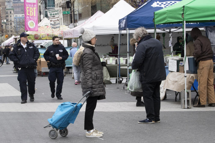 A shopper stands on a social distancing marking as police officers patrol the farmers market in Union Square, Wednesday, March 25, 2020, in New York. Police have stepped up efforts to pressure New Yorkers to practice social distancing at the epicenter of the crisis. It's part of a global challenge that law enforcement and health officials say is critical to containing the coronavirus. (AP Photo/Mary Altaffer)