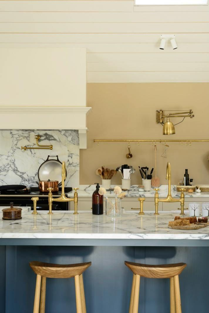 <p>These creamy light brown walls in a gorgeous deVOL kitchen make for the perfect backdrop. The deep blue-gray kitchen island mixed with cool marble surfaces and brass hardware is such a beautifully surprising combination with the strong, earthy walls. Swapping out hardware is an easy way to liven up an all-white kitchen. Choose brass to add a bit of elegance.<br></p>