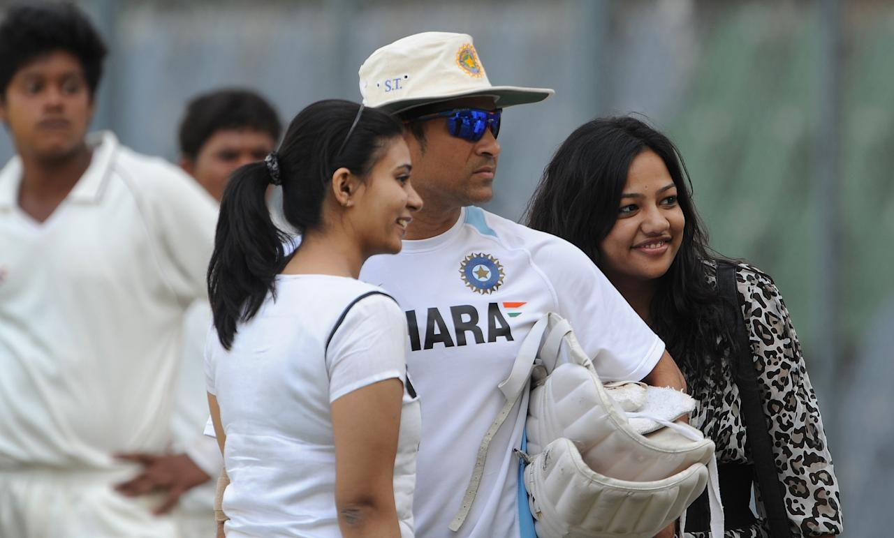 Indian cricketer Sachin Tendulkar (C) poses with fans prior to a team practice session at the Wankhede stadium in Mumbai on November 20, 2011. India plays third test cricket match against West Indies from November 22 in Mumbai. Tendulkar, the world's leading scorer in both Test and one-day cricket, needs just one more hundred to complete an unprecedented century of centuries, having already made 51 in Tests and 48 in one-day internationals. AFP PHOTO/Punit PARANJPE (Photo credit should read PUNIT PARANJPE/AFP/Getty Images)