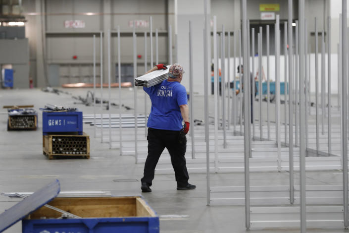 In this April 1, 2020, photo work continues at the TCF Center to build temporary hospital rooms in the convention center in Detroit. In the decade before Michigan and its largest city became the latest hotspot for the deadly coronavirus, officials were steadily cutting back on their first line of defense against pandemics and other health emergencies. Approaching bankruptcy, Detroit disbanded most of its public health department and handed its responsibilities to a private nonprofit. (AP Photo/Carlos Osorio)