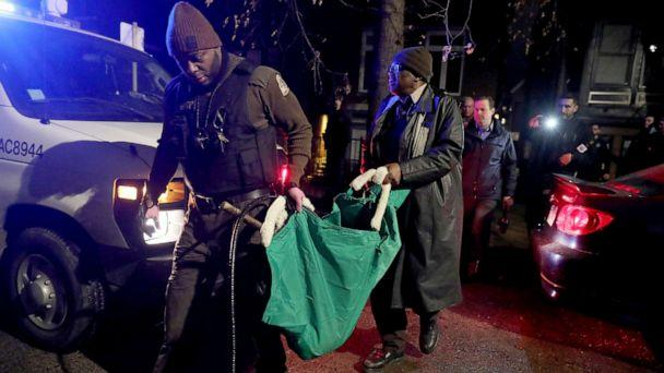 PHOTO: A Chicago police officer and a Chicago Animal Care and Control worker carry a coyote out in a green bag after tranquilizing the animal behind a home, Jan. 9, 2020. (Chris Sweda/Chicago Tribune via AP)