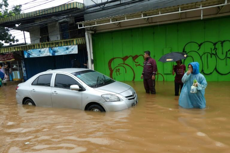 People walk past a car stuck in floodwaters in Jakarta