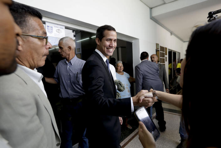 Venezuela's self-proclaimed interim president Juan Guaido shakes the hand of a supporter as he arrives for a meeting with electricity experts in Caracas, Venezuela, Thursday, March 28, 2019. The Venezuelan government on Thursday said it has barred Guaido from holding public office for 15 years, though the National Assembly leader responded soon afterward that he would continue his campaign to oust President Nicolas Maduro. (AP Photo/Natacha Pisarenko)