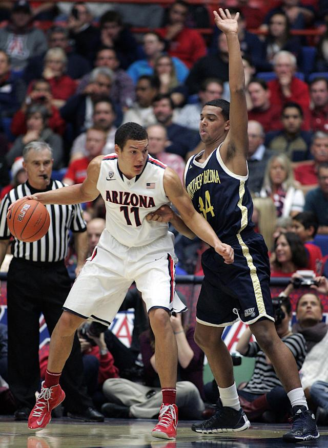 Arizona's Aaron Ashley (11) maneuvers against Northern Arizona's Jordyn Martin (34) for a shot during the second half of an NCAA college basketball game Monday, Dec. 23, 2013, in Tucson, Ariz. Arizona won 77-44. (AP Photo/John MIller)