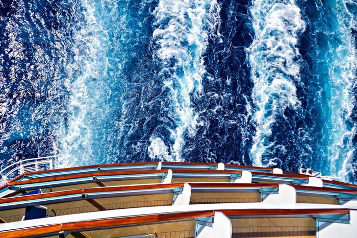 The large wake of a cruise ship is seen from the top of the ship.