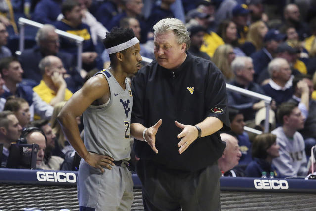 West Virginia coach Bob Huggins speaks with guard Brandon Knapper (2) after a play during the second half of an NCAA college basketball game against TCU on Tuesday, Jan. 14, 2020, in Morgantown, W.Va. (AP Photo/Kathleen Batten)