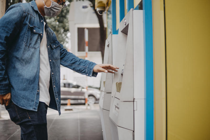 Young asian man wearing medical mask withdraw money from bank cash machine with debit card - Senior male doing payment with credit card in ATM - Concept of business, banking account and lifestyle people