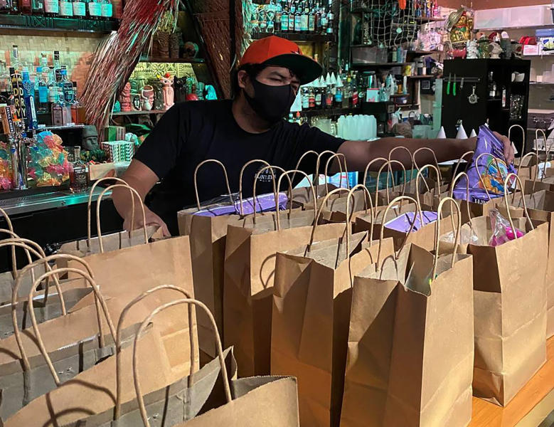 This photo provided by Lei Low Bar shows David Perez, organizing To-go orders at the Lei Low Bar in Houston on Thursday, June 25, 2020.  Businesses reopening across states after months of shutdown have been met with fanfare. But now that states like Texas, Arizona and elsewhere are seeing alarming surges in reported cases, businesses large and small face the quandary of deciding whether or not to close or scale back reopening -- this time, with little government guidance.