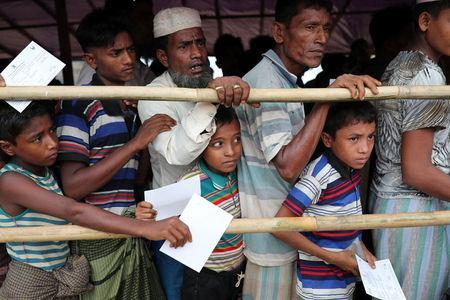 Rohingya refugees stand in a queue to collect meat from a relief distribution center in the Balukhali refugee camp in Cox's Bazar