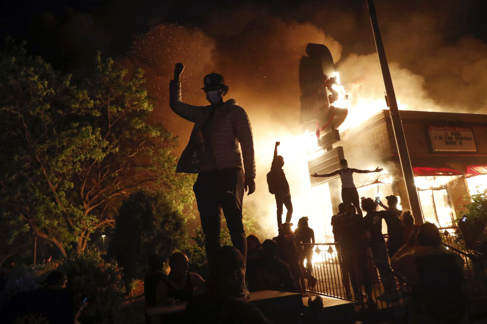 People demonstrate outside a burning Arby's fast food restaurant on May 29, 2020, in Minneapolis during a protest over the death of George Floyd. (AP Photo/John Minchillo)