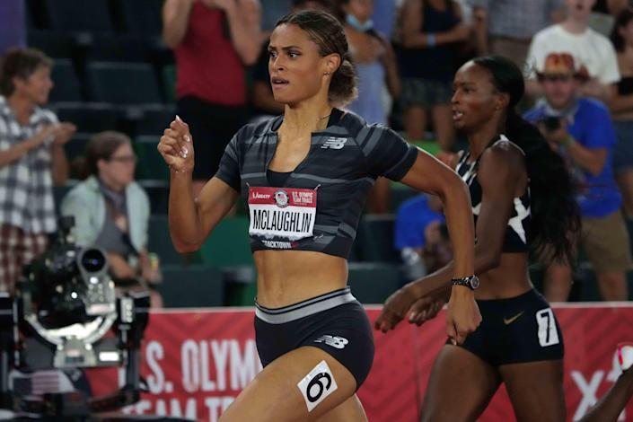 Sydney McLaughlin defeats Dalilah Muhammad to win the women's 400-meeter hurdles in a world-record time of 51.90 seconds.
