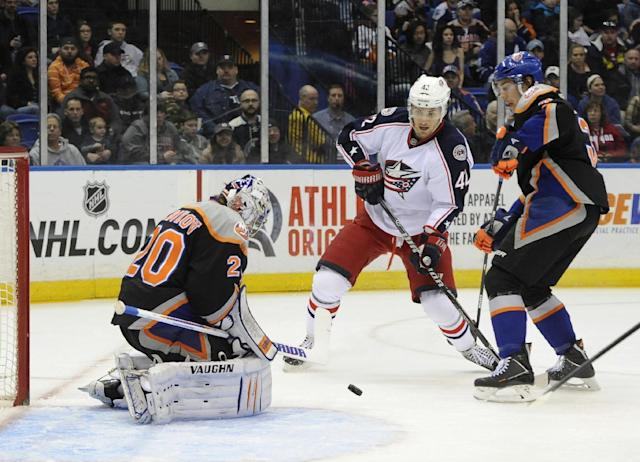 New York Islanders goalie Evgeni Nabokov (20) stops a shot on goal by Columbus Blue Jackets' Artem Anisimov (42) as Islanders' Travis Hamonic (3) defends from behind in the first period of an NHL hockey game on Sunday, March 23, 2014, in Uniondale, N.Y. (AP Photo/Kathy Kmonicek)