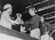 Queen Elizabeth presents the Jules Rimet Cup to Bobby Moore, captain of the England team, as her husband Prince Philip and hat trick hero Geoff Hurst look on after England beat West Germany 4-2 World Cup final 1966 at Wembley stadium. (STAFF/AFP via Getty Images)