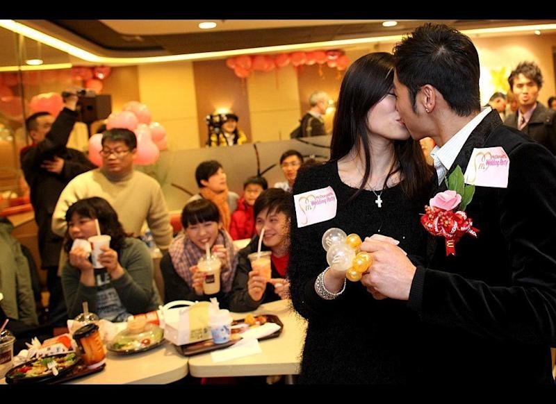"""Kelvin Kwong, right, and Ashley Tse kiss during a Valentine's Day engagement party at a McDonald's fast-food restaurant in Hong Kong on Feb. 14. Thrown as a surprise by the groom, the function was the first of its kind for McDonald's, which hopes that its """"Wedding Party"""" will appeal to loved-up couples looking for a bride with their Big Mac. For around $1,300, potential customers can expect food and music for up to 50 guests."""