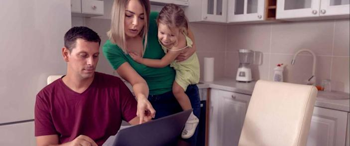 Worried young parent calculating bills at home