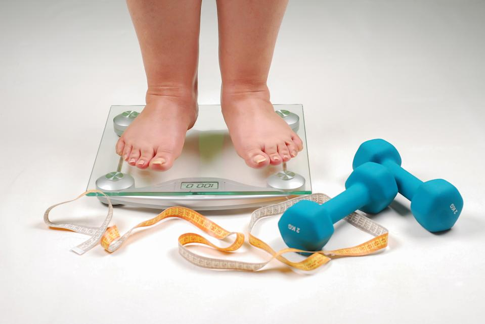 feet on scales next to weights and tape measure