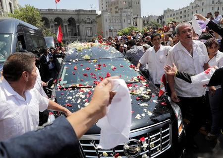 The hearse carrying the remains of Peru's former President Alan Garcia, who killed himself this week, makes its way through the crowd of supporters, in Lima, Peru April 19, 2019. REUTERS/Guadalupe Pardo