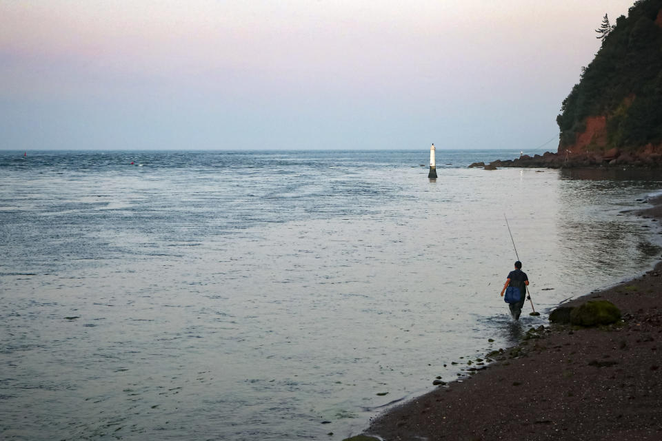 A man walks along the beach to take get a better spot to fish from in Shaldon, Devon, England, Thursday July 22, 2021. (AP Photo/Tony Hicks)