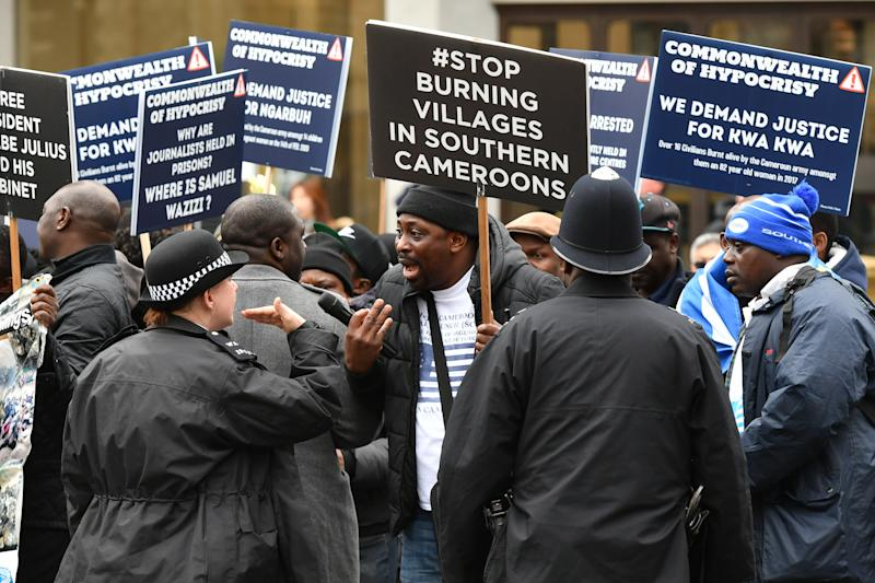 Police officers speak with demonstrators holding placards with messages about Cameroon outside Westminster Abbey, London, ahead of the Commonwealth Service.