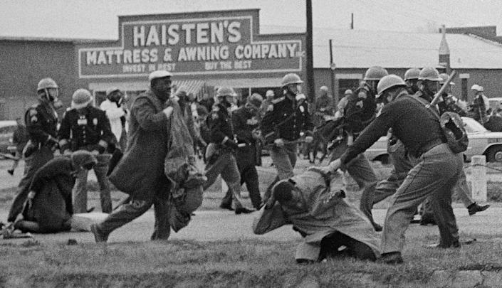 """In the foreground of this photo from Selma's """"Bloody Sunday,"""" John Lewis  is being beaten by a state trooper. Lewis  suffered a fractured skull."""