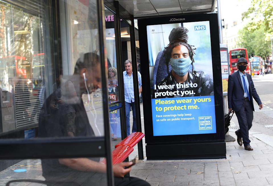 A man wearing face covering walks pass a screen on a bus stop in London displaying a NHS notice telling travellers to wear face covering for their safety on public transport, as face coverings becomes compulsory on public transport in England. Picture date: Friday August 7, 2020.