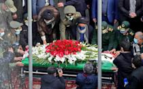Iranian officials pray over the coffin of slain top nuclear scientist Mohsen Fakhrizadeh during his funeral ceremony in the capital Tehran, in a picture supplied by the conutry's defence ministry